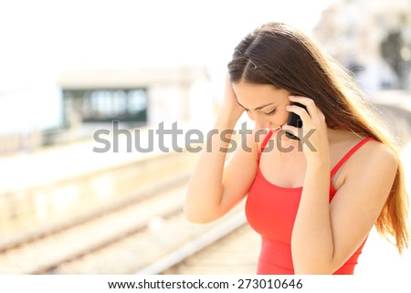 Traveler talking on the mobile phone in a train station - stock photo