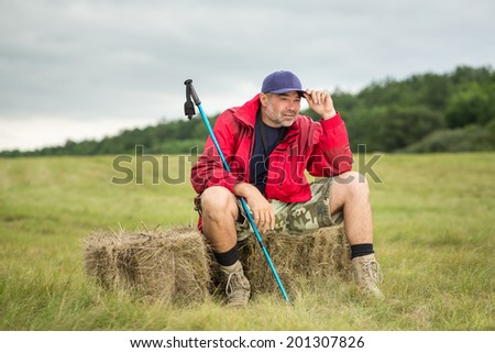 Traveler trekker enjoying a valley view while sitting resting after a trail - stock photo