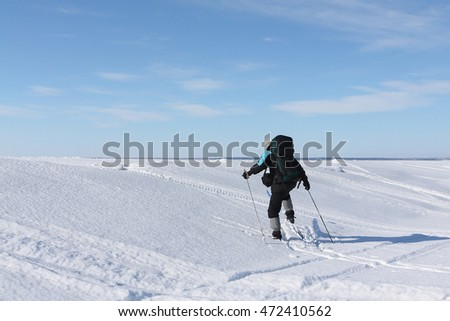 traveler with a backpack skiing on the frozen river