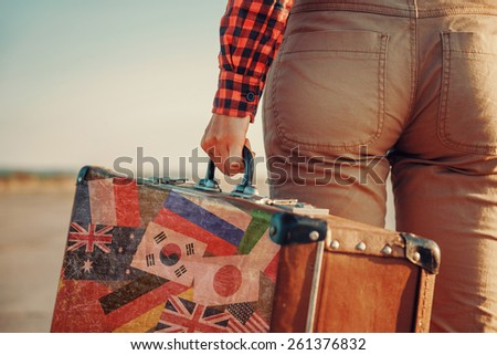 Traveler with a suitcase. Suitcase with stamps flags of different country - stock photo