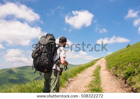 traveler with backpack and trekking poles on the road close up