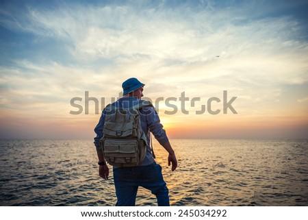 traveler with backpack near sea looking far away at horizon at beautiful sunset - stock photo