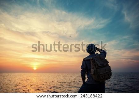traveler with backpack near sea looking far away at horizon at sunset - stock photo