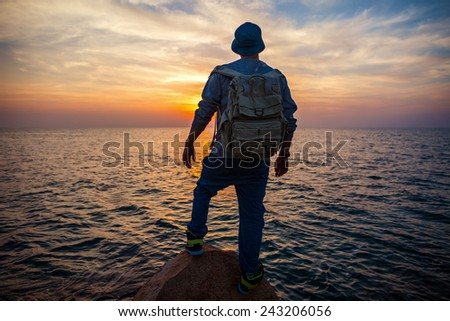 traveler with backpack near the sea looking far away at the horizon at sunset - stock photo