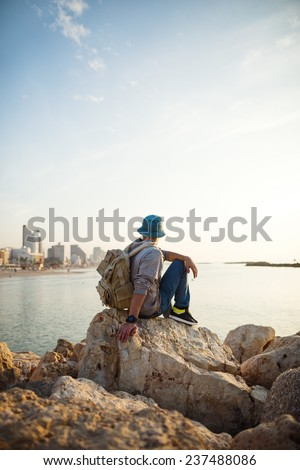 traveler with backpack sitting on the rocks near the sea on the beach in the city and looking far away at the horizon - stock photo