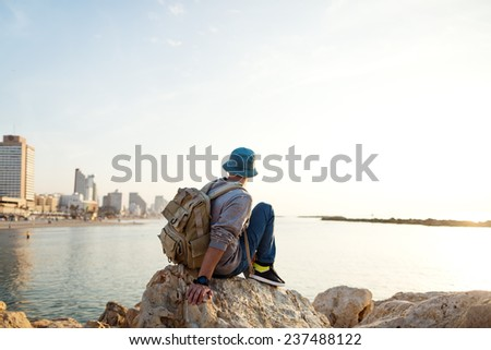 traveler with backpack sitting on the rocks near the sea on the beach in the city and looking far away