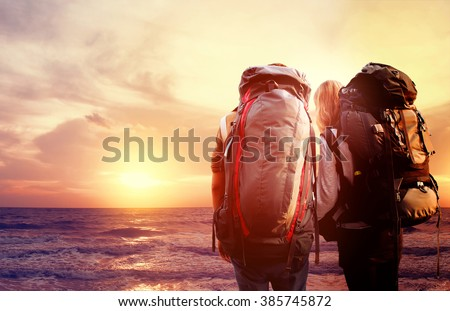 traveler with backpack walking over bridge and sunlight with sea sunset background [Blur and Select focus background] - stock photo