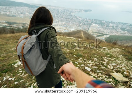 Traveler woman holding man's hand and leading him on nature outdoor. Couple in love. Focus on woman. Point of view shot - stock photo