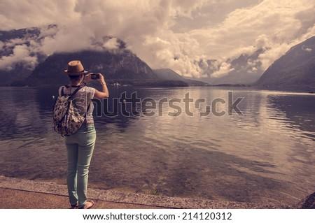 Traveler woman taking photo of amazing landscape - stock photo