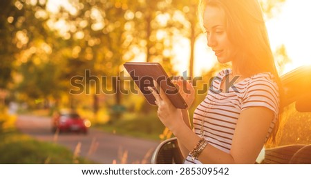 Traveler woman using tablet on car road trip vacation travel. Young woman reading guide book map on tablet computer pc, using mobile internet, relaxing by the car with sunlit road in background.  - stock photo