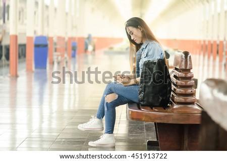 traveler woman waits train on railway platform. - stock photo