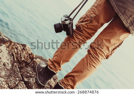 Traveler woman with old photo camera standing on stone coast near the sea. View of legs. Image with instagram filter - stock photo