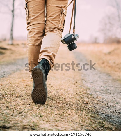Traveler woman with old photo camera walks on a road, face is not visible - stock photo