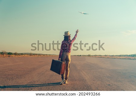 Traveler woman with vintage suitcase waves her hand to airplane, rear view, theme of travel. With vintage filter - stock photo