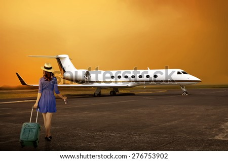 Traveler woman with walk with suitcase into private jet airplane. Travel concept - stock photo