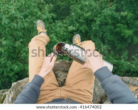 Traveler young man sitting on top of rock over the summer forest and pouring tea from thermos to cup. Point of view shot - stock photo