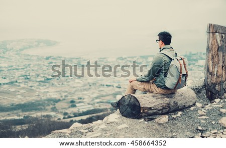 Traveler young man sitting on tree trunk and looking at town. Toned image