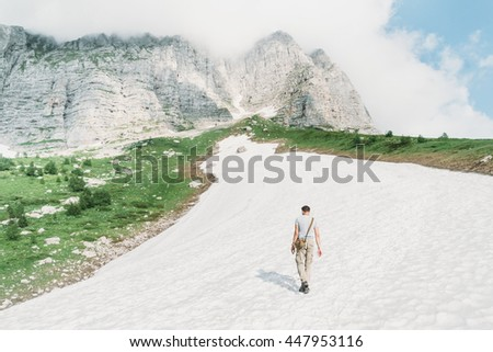 Traveler young man walking on snow path in the mountains in summer season outdoor, rear view - stock photo