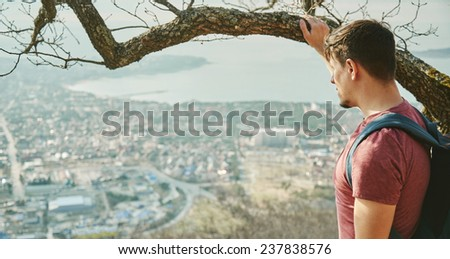 Traveler young man with backpack looking at the city from hill. Concept of tranquil life from the urban bustle - stock photo