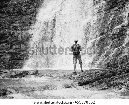 Traveler young man with backpack looking at waterfall in summer outdoor, rear view. Monochrome image - stock photo