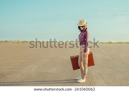 Traveler young woman in hat and sunglasses standing with a suitcase on road in summer