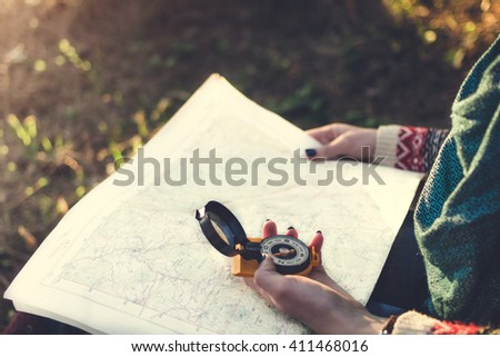 Traveler young woman searching direction with a compass on background of map in the forest - stock photo