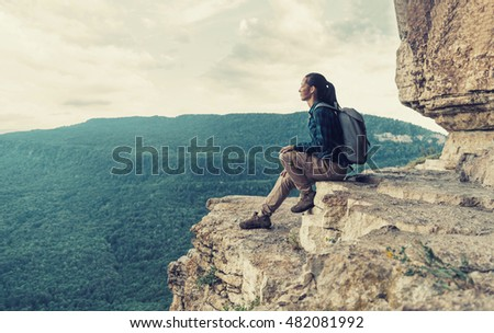 Traveler young woman sitting high on cliff Eagle shelf and enjoying view of nature in summer, Mezmay, Krasnodar region, Russia