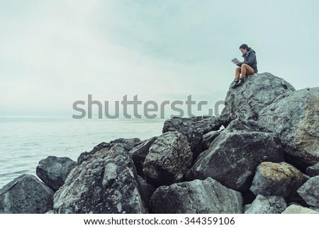Traveler young woman sitting on big stone with digital tablet near the sea. Concept of technology and travel. Space for text in the left part of image