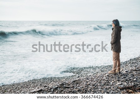 Traveler young woman standing on pebble coast and looking at sea waves in windy weather