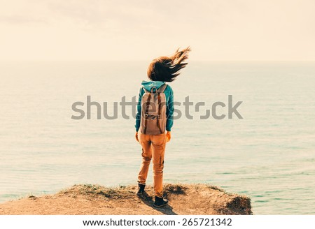 Traveler young woman with backpack standing on coastline near the sea in windy weather, her hair fluttering in the wind - stock photo