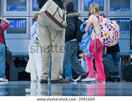 Travelers and businesspeople glance at the departure and arrival information at an airport - stock photo