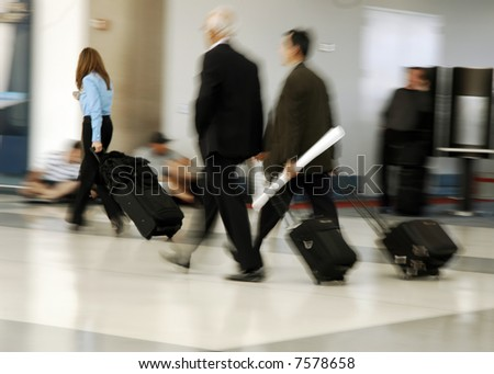 Travelers in motion rushing through an airport - stock photo