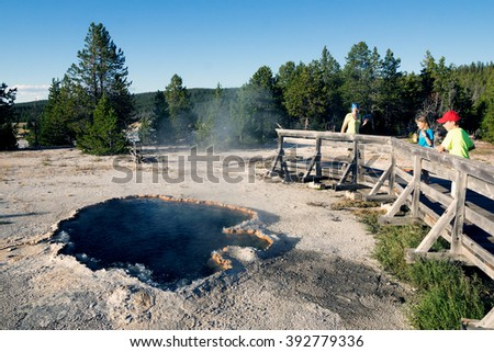 Travelers look at Surprise Pool, Lower Geyser Basin, Yellowstone National Park, United States - stock photo