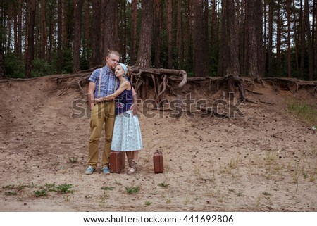 travelers, man and woman standing arm in arm in the woods with a suitcase