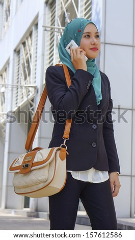 traveling business woman walking on train station platform with travel bag using mobile phone - stock photo