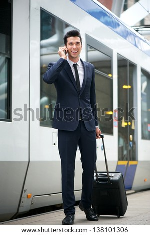 Traveling businessman talking on the phone at metro station with train in background - stock photo