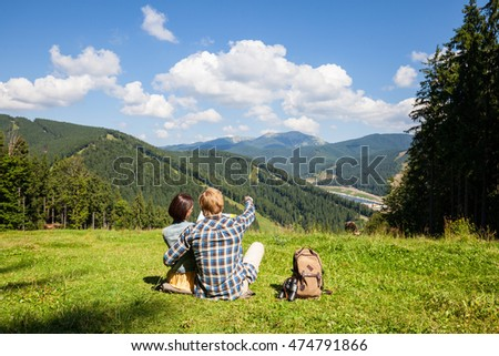 Traveling couple sitting on the alpine meadow and looking at the map