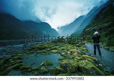 traveling man take a photograph in franz josef glacier important traveler destination in south island new zealand - stock photo