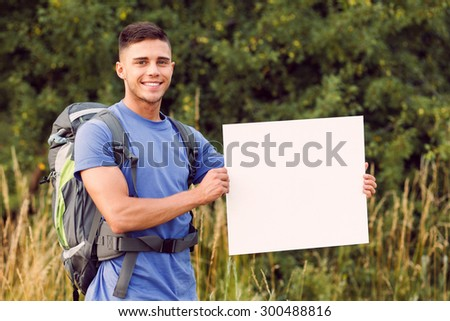 Traveling. Portrait of a young handsome tourist wearing blue t-short and backpack standing looking at the camera smiling and holding copy space - stock photo