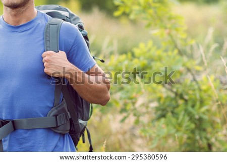Traveling. Portrait of a young tourist wearing blue t-short holding his backpack standing in the forest - stock photo