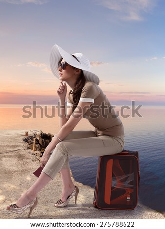 Traveling stylish woman sitting on her luggage on the pierce near the sea while holding her passport and dreaming. Travel,vacation,tourism concept.
