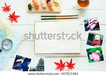 Traveling to Japan / memories of Japan concept. Map, polaroid photo, sushi set, green tea, red maple leaves, blank notebook on a white table. Copy space. - stock photo