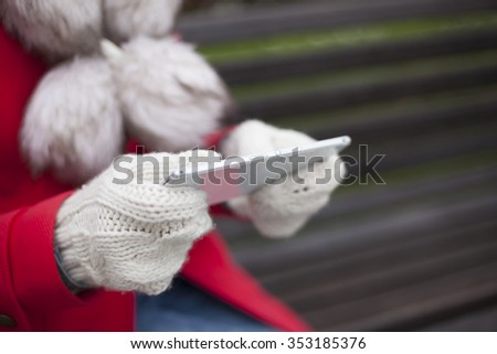 Traveling woman with mobile phone, cold weather - stock photo
