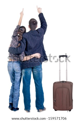 traveling young couple with suitcas pointing at wall. Back view people. Isolated over white background.
