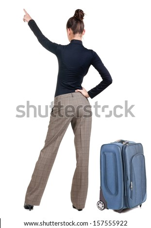 traveling young woman with suitcas pointing at wall. Rear view. Isolated over white backrgound. - stock photo