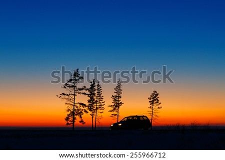 Traveller car against the bright sunset. - stock photo