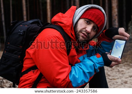 Traveller in the forest shows map in his phone  - stock photo