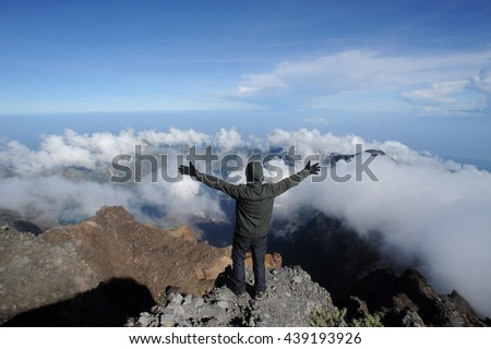 Traveller reach at top of Mount Rinjani with Volcano janu bari and lake Segera anak view, Lombok - Indonesia