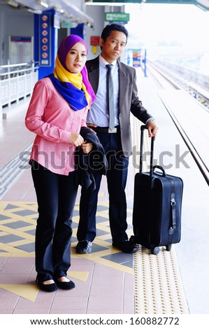 Travelling business executives waiting for train