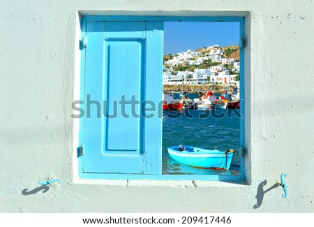 Travelling concept - window into beauty of Greece and Cyclades islands showing old port of Mykonos and colorful boats - stock photo